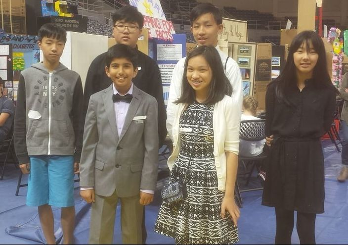A group of students standing in front of Social Studies Fair projects at the Louisiana State Social Studies Fair