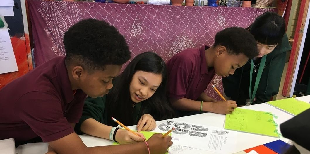 Two female students and two make students are working on an art project. They are drawing in a booklet.