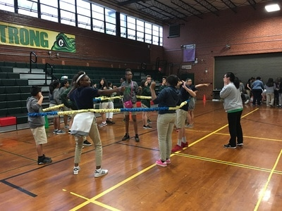 A group of students in the gym playing a game with a large, stretchy rope.