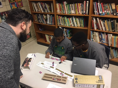 A volunteer assists two male students working with a laptop and robotics equipment.