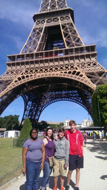 Students and adults in front of the Eiffel Tower.