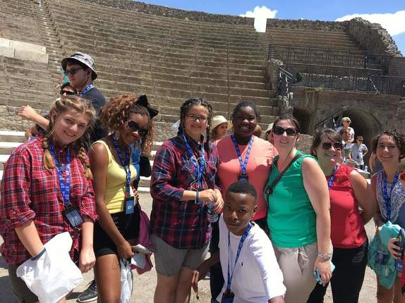 A group of students and adults in the Colosseum. They are smiling and happy.