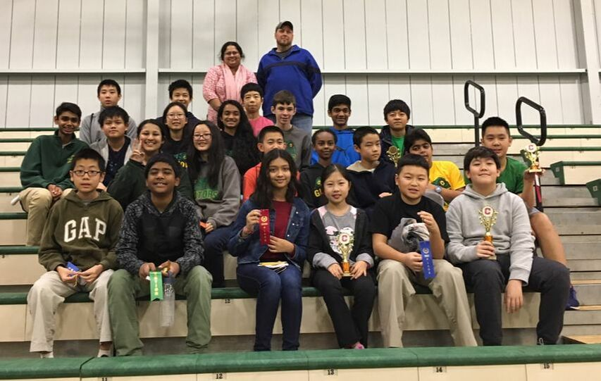 A large group of students and chaperones posing on the stairs at the Catholic High School math competition. Some students are holding trophies.